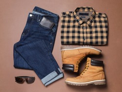 Flat lay composition with stylish men's clothes and boots on brown background