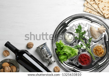 Flat lay composition with symbolic Passover (Pesach) items and meal on wooden background, space for text #1325633810