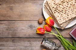 Flat lay composition with symbolic Pesach (Passover Seder) items on wooden table, space for text