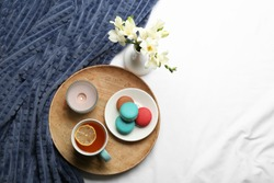 Flat lay composition with tea and warm plaid on white bedsheet, space for text