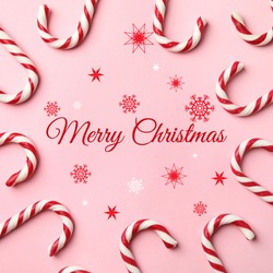 Flat lay composition with text MERRY CHRISTMAS and candy canes on pink background