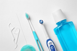 Flat lay composition with toothbrushes and oral hygiene products on white background