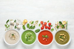Flat lay composition with various soups, ingredients and space for text on white background. Healthy food