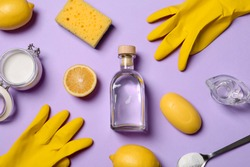 Flat lay composition with vinegar and cleaning supplies on color background