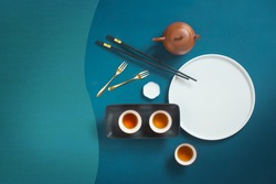 Flat lay conceptual mid-autumn festival food and drink mooncake and tea on blue fabric texture background. Text space image.