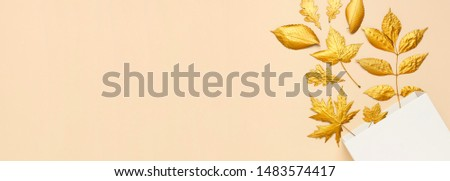 Flat lay creative autumn composition. White Gift Paper package and Golden leaves on beige background top view copy space. Fall concept. Autumn background. Minimal concept idea, floral design.