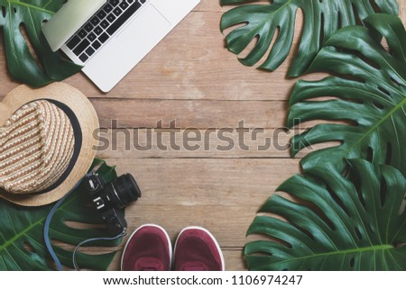 Flat lay creative frame of tropical nature leaves Monstera on rustic wood grunge background with laptop computer, retro camera, hat and pair of sneaker shoes, digital nomad and life balance concepts.