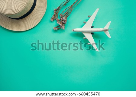 Flat lay design of travel concept with plane, straw hat on green background with copy space.