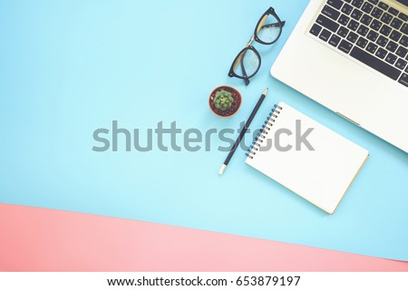Flat lay design of work desk with labtop, notebook, glasses and cactus on pink and blue background.