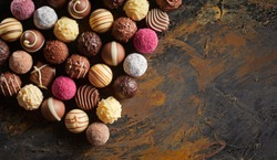 Flat lay display of luxury handmade chocolates arranged in neat rows on rustic wood with copy space viewed high angle