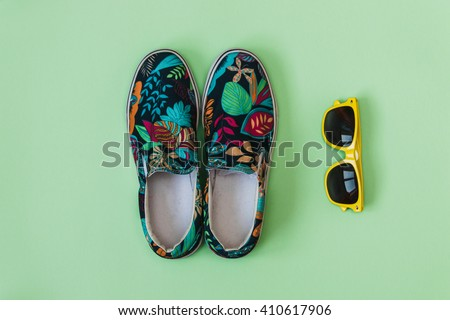 Flat lay fashion set: colored slippers shoes with palm and flowers print and yellow sunglasses on pastel background. Top view. #410617906