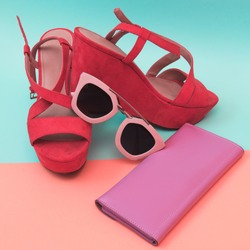 Flat lay fashion set:  shoes with sunglasses and pink purse on pastel backgrounds. Top view.