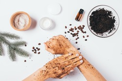Flat lay female hands making peeling procedure with homemade cosmetic coffee scrub with clay and pine essential oil next to ingredients on white table.