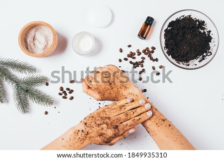 Flat lay female hands making peeling procedure with homemade cosmetic coffee scrub with clay and pine essential oil next to ingredients on white table. Stock photo ©
