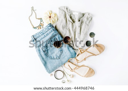 flat lay feminini clothes and accessories collage with shirt, jeans shorts, sunglasses, bracelet, sandals, earrings on white background.