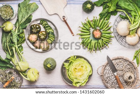 Flat lay green vegetables in bowls on light table with knife: green peas, kohlrabi, lettuce, zucchini, cucumber, green tomatoes. Top view. Clean vegetarian eating and cooking concept.  Foto stock ©