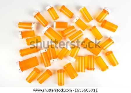 Flat lay group of empty plastic orange prescription bottles on their side, some with lids some without, on white.