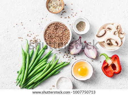 Flat lay healthy vegetarian food ingredients for lunch on a light background, top view. Buckwheat, green beans, sweet peppers, red onion, mushrooms - clean eating vegetarian food concept