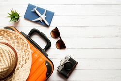 Flat lay holidays and traveler concept on white wooden table background with plane and passport on orange suitcase , hat and sunglasses, Top view with copy space