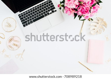 Flat lay home office desk. Female workspace with laptop, pink peonies bouquet, golden accessories, pink diary on white background. Top view feminine background. Fashion blog hero. #708989218