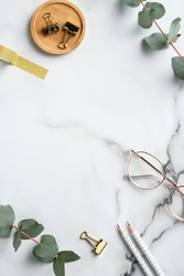 Flat lay home office desk table. Feminine workspace with glasses, office supplies, greenery on marble background. Elegant freelancer workplace
