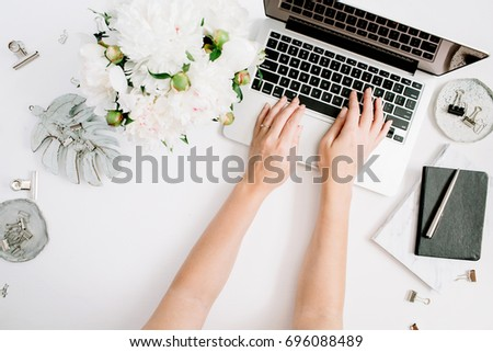 Flat lay home office desk. Women workspace with female hands, laptop, white peony flowers bouquet, accessories, marble diary. Top view feminine background. Girl working on laptop.