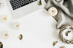 Flat lay home office desk. Workspace with laptop, white pumpkins, cotton branches, grey plaid and wreath frame. Top view autumn or winter composition.