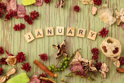 Flat lay image featuring border of various dried flowers surrounding wooden letters spelling the word January with copy space