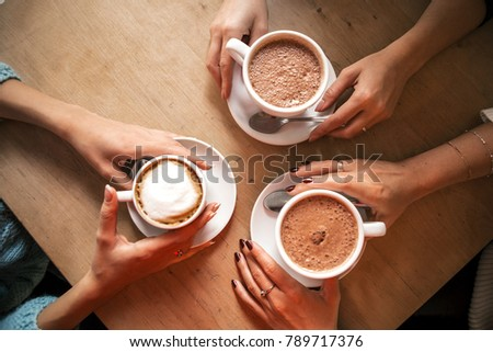 Flat lay image from above: three hands holding three cup of coffee on a wooden table. Cozy, lifestyle image