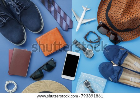 Flat lay image of accessory clothing man or women to plan travel in holiday background concept.Mobile phone & passport with items in vacation season.Table top view object on blue paper.Pastel tone.