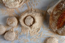 Flat lay image of bread loaves, dough ingredients, a bowl of flour, a sourdough bread on marble kitchen countertop. A dough loaf is dropped onto a pile of flour creating a crater and a big splash.
