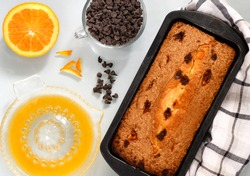flat lay image of chocolate and orange cake in a baking tin with choc chips by the side  light background