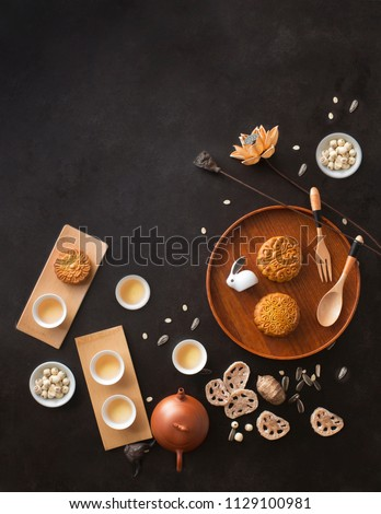 Flat lay mid autumn festival food and drink on rustic black background. Text space image.