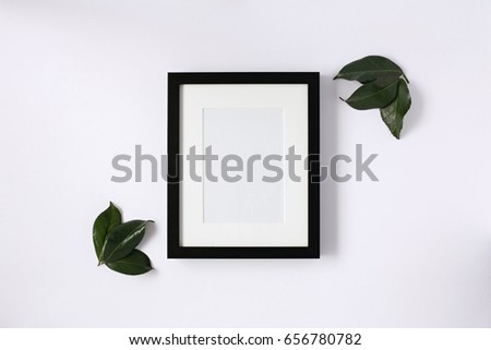 Flat lay mock up. Black photo frame and leaves on a white desktop.