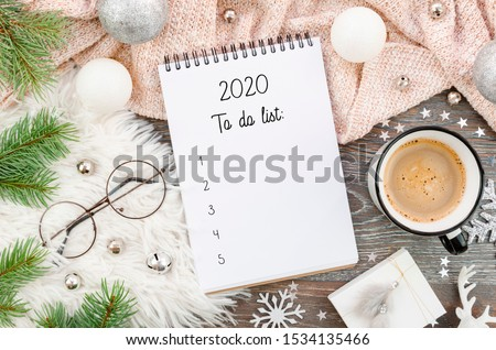 Flat lay New Year decorations and blank white spiral notebook with to-do list framed with cozy winter decor, tree branches, coffee and xmas toys. Planning, wish list 2020 concept