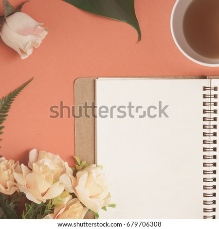 flat lay notebook and rose...