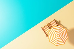 Flat lay of a composed miniature of beach lounge area with umbrella and sunbeds on the colorful surface.