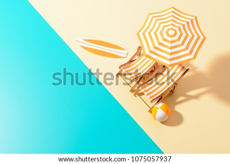 Flat lay of a composed miniature of beach lounge area with umbrella and sunbeds on the colorful surface. #1075057937