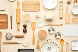 Flat lay of assorted wooden and ceramic utensils and containers placed on beige background
