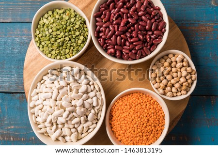Flat lay of assortment of peas, lentils, beans and legumes over blue wooden background.