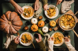 Flat-lay of Autumn dinner for gathering or Thanksgiving Day celebration. Family or friends eating butternut squash pasta with sausage and sage over tablecloth decorated with pumpkins, top view