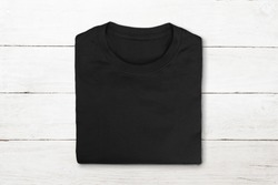 Flat lay of black folded tshirt on vintage white wooden background