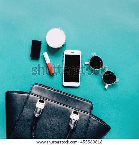 Flat lay of black leather woman bag open out with cosmetics, accessories and smartphone on green background