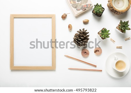 Flat lay of blank wooden picture frame with a collection of modern interior decor objects