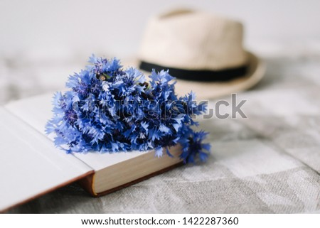Flat lay of bouquet of blue cornflowers, straw hat and a book. Summer background #1422287360