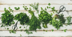 Flat-lay of bunches of various fresh green kitchen herbs. Parsley, mint, dill, coriander, rosemary, thyme over white wooden background, top view. Spring or summer healthy vegan cooking concept