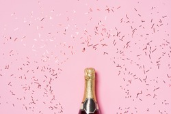 Flat lay of Celebration. Champagne bottle with colorful party streamers on pink background.
