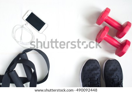 Flat lay of cellphone, red dumbbells and sport equipment on white background. Sport wear, Sport fashion, Sport accessories, Sport equipment, top view