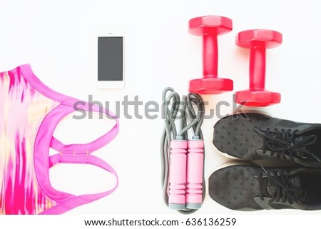 Flat lay of cellphone with pink sport bra, Jump rope and red dumbbells on white background, Workout and Healthy concept, Top view