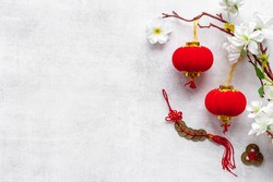 Flat lay of Chinese New Year decoration flowers and red lanterns